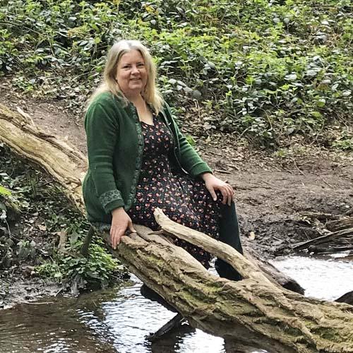 Isabel Arends sitzt im Wald auf einem Baumstamm an einem Bach und lächelt in die Kamera