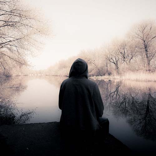 Einsamer Mensch am winterlichen See